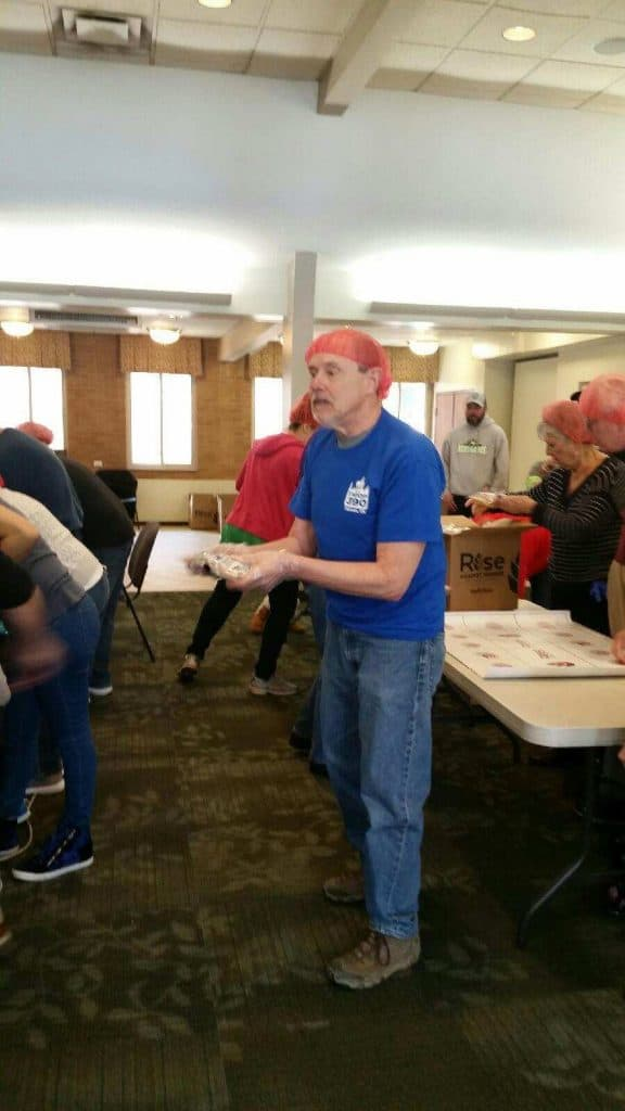 Scout leader packing food for Rise Against Hunger